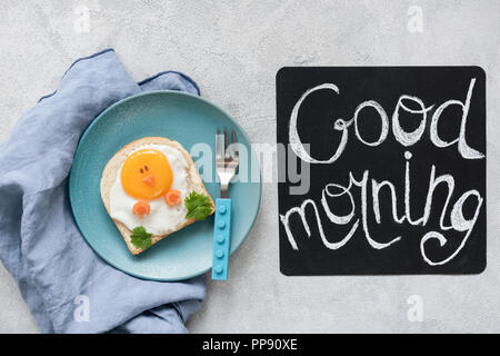 Breakfast food kids. Funny toast with egg and good morning text on a chalkboard. Top view - Stock Photo