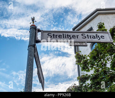 Berlin, Mitte, Miniature Street art. Small cork yogi man on Strelizer strasse & Anklamer strasse sign - Stock Photo