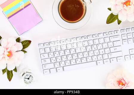 Pink flowers, clock on a white desktop next to a mug of coffee and a keyboard. Top view, flat layout. Copy the space - Stock Photo