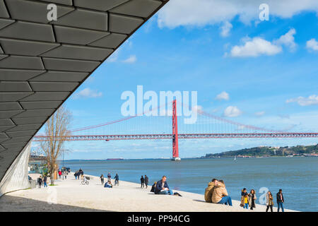 25 April Bridge, former Salazar bridge, over the Tagus river viewed from the MAAT – Museum of Art, Architecture and Technology, Lisbon, Portugal - Stock Photo