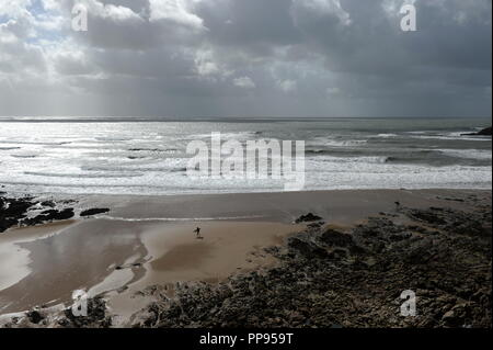 Beach overview on a stormy day . A surfer is walking up the beach - Stock Photo