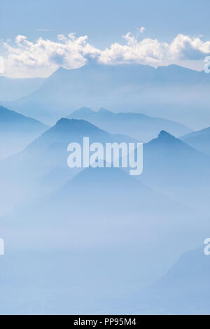 Blue layers of mountain ridges in the french alps with clouds. - Stock Photo