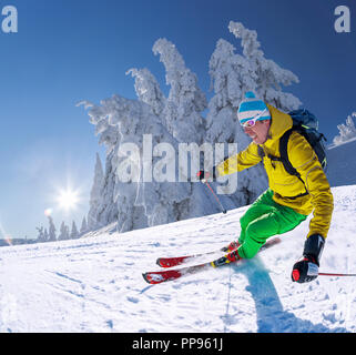 Skier skiing downhill in high mountains against blue sky - Stock Photo