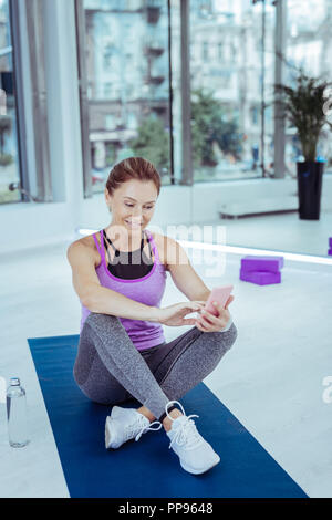 Pleased mature woman taking selfie during training - Stock Photo