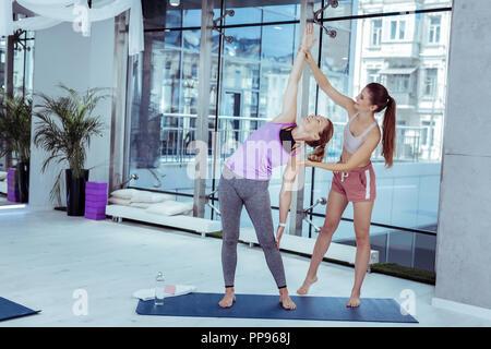 Optimistic female trainer guiding woman during yoga - Stock Photo
