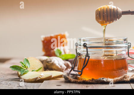 Honey in jar with honey dipper, ginger and lemon on wooden background - Stock Photo