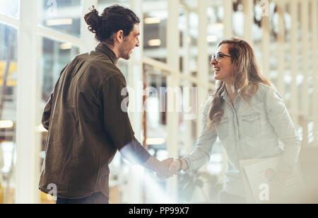 Happy business colleagues greeting each other by shaking hands at work place. Businesswoman carrying office papers shaking hand with a business collea - Stock Photo