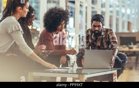 Business partners in a meeting discussing ideas sitting in office. Businessman working on laptop sitting with female coworkers in office. - Stock Photo