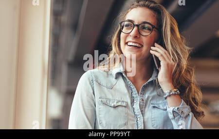 Smiling businesswoman talking on mobile phone in office. Cheerful woman entrepreneur on a phone call in office. - Stock Photo