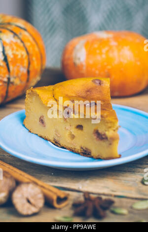 Homemade sliced pumpkin tart pie recipe with cinnamon, nuts and fresh pumpkin on vintage table wooden table background. Halloween party traditional d - Stock Photo