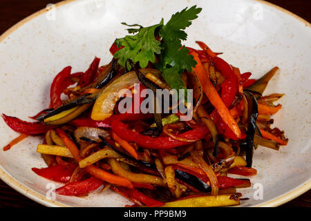 Vegetable saute with coriander over wooden - Stock Photo