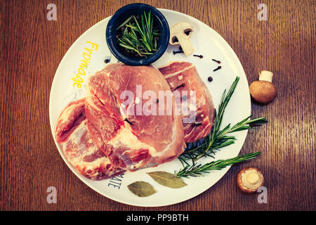 Two pieces of raw pork tenderloin, rosemary on a white plate with mushrooms, top view - Stock Photo
