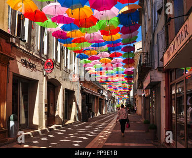 Colourful umbrellas cover a shopping street in Carcassonne, Aude, Occitanie, France - Stock Photo