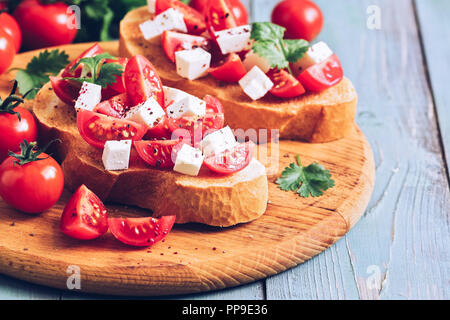 Bruschetta with tomatoes, cheese and greens on toasted bread. Traditional Italian food. Selective focus - Stock Photo