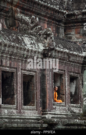 Buddhist monk meditating in window of temple building at Angkor Wat complex in Siem Reap, Cambodia - Stock Photo
