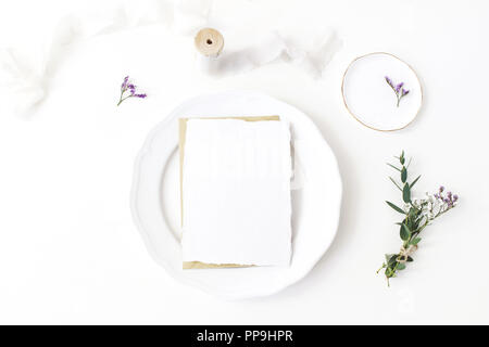 Festive wedding, birthday table setting with porcelain plate, silk ribbons and floral bouquet of eucalyptus, limonium flowers. Blank card mockup. Rustic restaurant menu concept. Flat lay, top view - Stock Photo