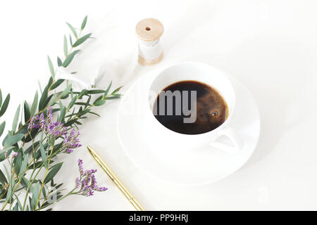 Wedding styled stock photo. Breakfast still life with eucalyptus leaves, limonium, baby's breath Gypsophila flowers, golden pen and cup of coffee. Floral composition. Selective focus. - Stock Photo