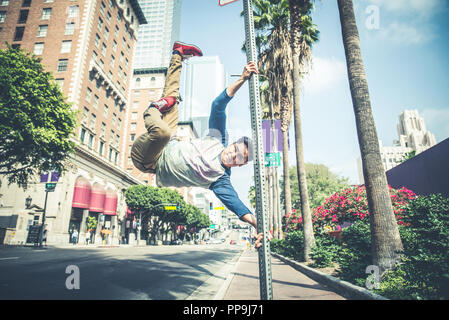 Parkour man doing tricks on the street - Free runner training his acrbatic port outdoors - Stock Photo