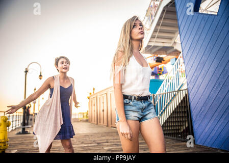 Two young women having argument. Angry fury girls screaming at each other - Stock Photo