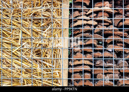 Close-up part of craft hotel or house for wild bees and other insect made of natural eco materials. Shelter made of cones, wood and bamboo sticks, hay, straw and bark - Stock Photo
