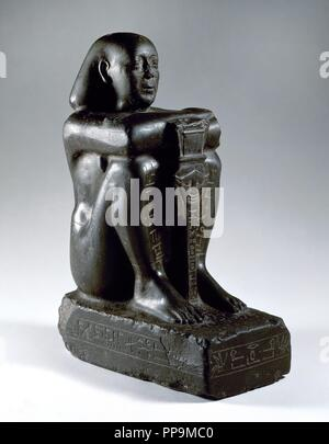 Block statue of Harsomtusemhat (664-610 B.C.) sitting on a socle, with his legs grouped and the hands on his knees. He is holding the sesheshet sistrum, with the face of the goddess Hathor. Basalt. 26th Dynasty. Lower Egypt. Archaeological Museum. Madrid. Spain. - Stock Photo