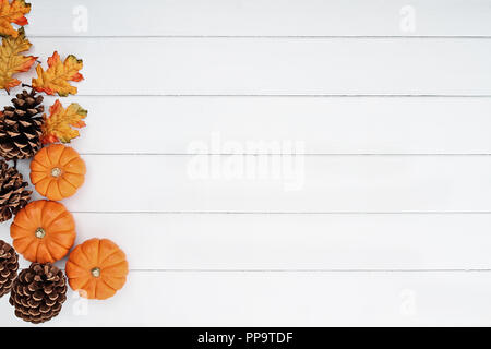 Rustic fall background of autumn leaves, pine cones and mini pumpkins with free copy space for text over a white rustic background. - Stock Photo