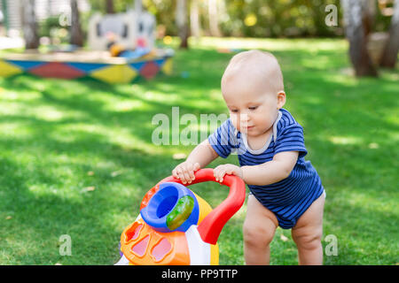 Cute little boy learning to walk with walker toy on green grass lawn at backyard. Baby laughing and having fun making first step at park on bright sunny day outdoors. Happy childhood concept - Stock Photo