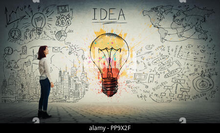 Side view of a pensive young woman looking at the wall with colorful light bulb and business sketch. Uniqueness of the idea and genius concept. - Stock Photo