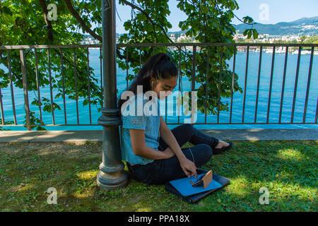 Girl sitting in a park with smartphone - Mädchen, das in einem Park mit Smartphone sitzt - Ragazza seduta in un parco con smartphone - Stock Photo