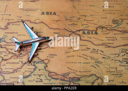 Airplane over the map of Asia close-up. Toy airplane on the map background. - Stock Photo