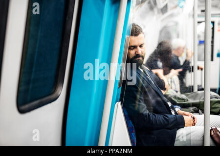 Sleeping hipster businessman inside the subway in the city, travelling to work. - Stock Photo