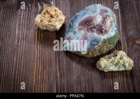 Amethyst crystals in blue smoky quartz on a dark wooden background - Stock Photo