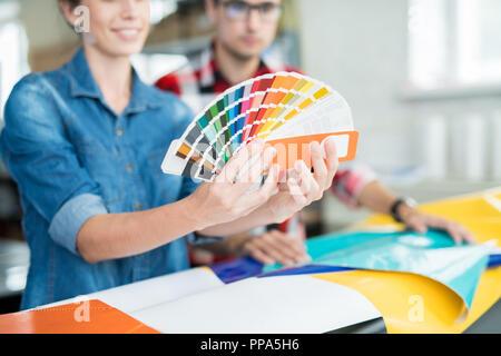 Crop coworking designers choosing colors - Stock Photo