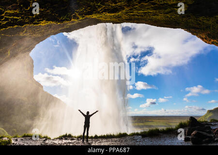Happy female traveler feeling the power of Seljalandsfoss waterfall in the South of Iceland, person standing behind the stream, famous Icelandic landm - Stock Photo