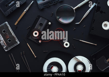 Flat lay audio and video cassette parts on dark background, top view of retro technology and media concept - Stock Photo