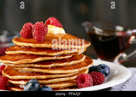 Stack of pancakes with berries and maple syrup - Stock Photo