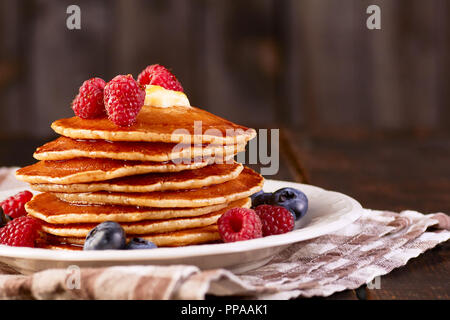 Pancakes with berries and maple syrup on dish over textile napkin - Stock Photo