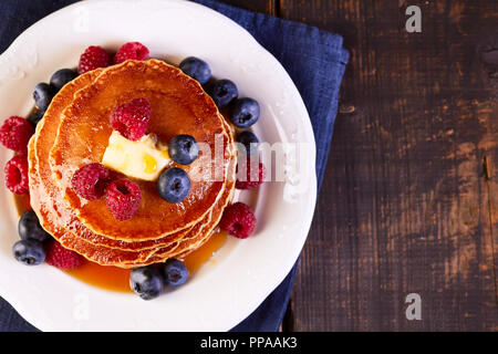 Pancakes with fresh berries maple syrup and butter on wooden table - Stock Photo