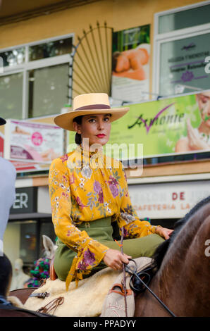 Woman in traditional costume riding horse, celebration, event, Fuengirola, Andalusia, Spain - Stock Photo