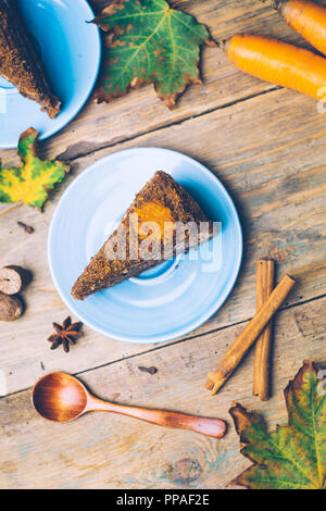 Carrot cake (homemade desserts) with cinnamon sticks and decorated with spices on wooden background - Stock Photo
