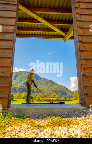 Golfer on Driving Rang in a Sunny Day with Mountain in Switzerland. - Stock Photo