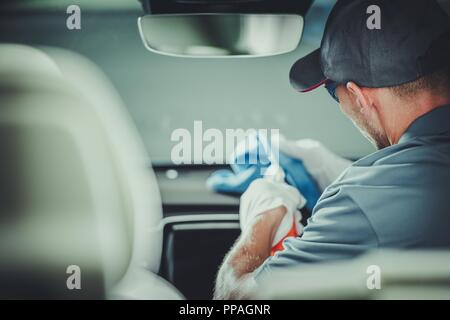 Modern Car Interior Cleaning and Detailing by Professional Caucasian Cleaner. - Stock Photo