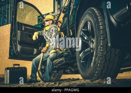 Caucasian Construction Industry Worker in His 30s Relaxing After Hard Working Day. Worker and His Black Pickup Truck. Industrial Theme. - Stock Photo