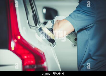 Professional Vehicle Buffing by Caucasian Car Detailing Service Worker. Removing Scratches From the Car Body Paint. Auto Polishing. - Stock Photo