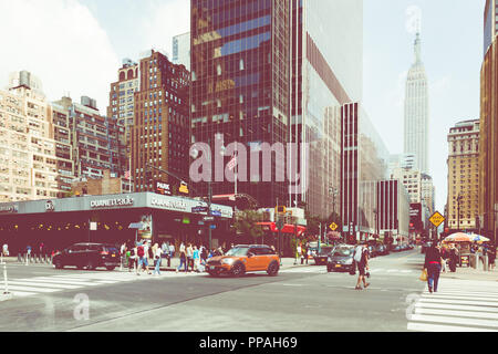 NEW YORK - SEPTEMBER 2, 2018: New York City street road in Manhattan at summer time, many cars, yellow taxis and busy people walk to work. - Stock Photo
