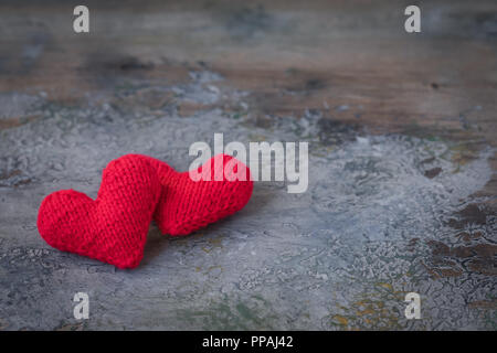 Valentine's Day red knitted wool hearts on concrete background, toned - Stock Photo