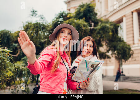 Two women tourists searching for right way using map in Odessa by opera house. Happy friends travelers pointing on direction - Stock Photo