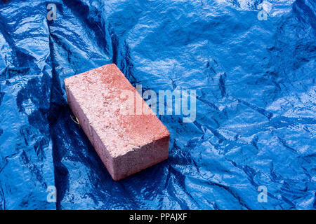 Berlin, Germany, September 22, 2018:  Close-Up of Red Brick on Blue Tarpaulin - Stock Photo