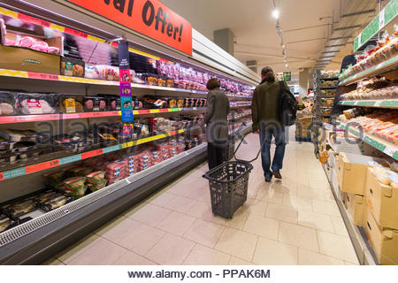Woman looking at packaged meats in refrigerated display case inside Lidl discount supermarket, Moore Street, North City, Dublin, Leinster, Ireland - Stock Photo