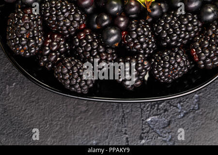 Photo on top of blackberries, black currant on black plate on black empty background - Stock Photo